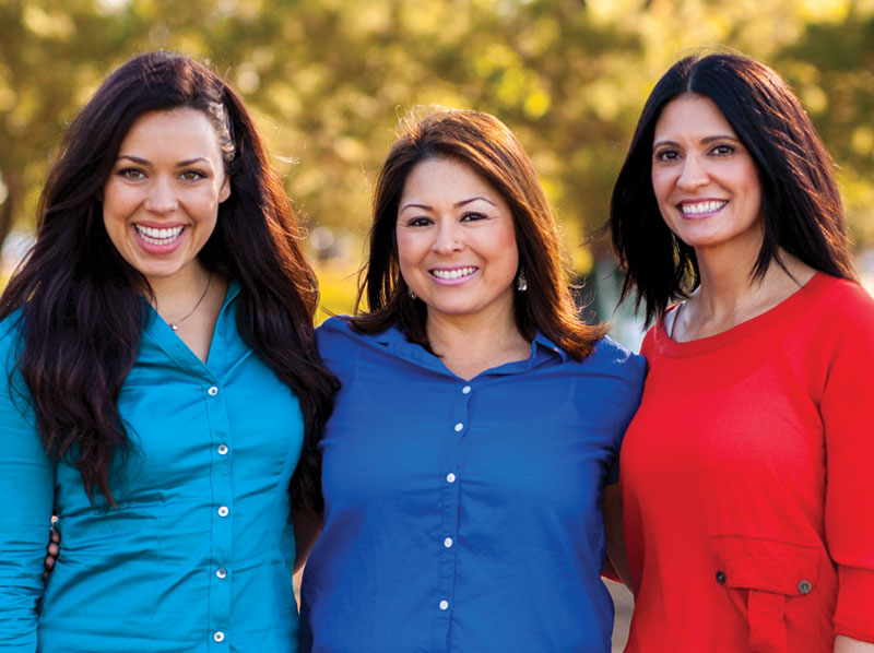 A group of three lady friends smiling in the outdoors.