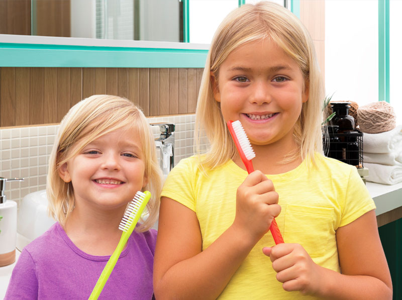 Two young girls in a bathroom, smiling and holding giant toothbrushes.